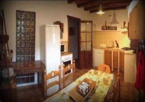 Vista de la cocina desde la derecha con nevera, horno y microondas