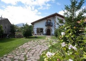 Camino de piedra, flores y casa blanca