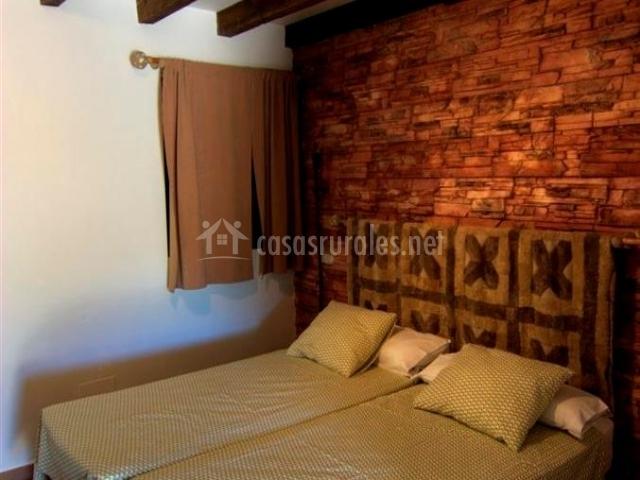 Dormitorio con camas individuaales y muro de ladrillo cocido