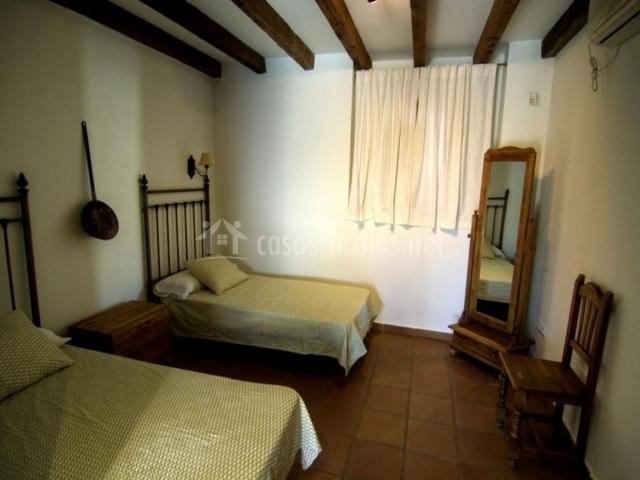 Dormitorio con camas individuales y espejo