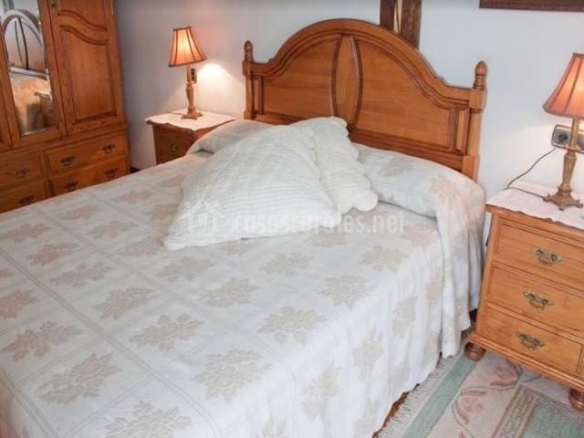 Dormitorio de matrimonio elegante con mesillas de madera y cabeceros