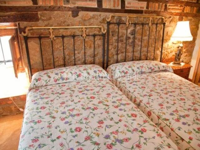 Dormitorio doble con camas juntas y colchas de flores
