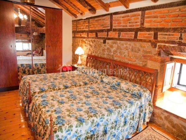 Dormitorio doble con paredes de ladrillo visto