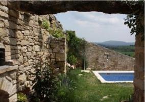 Fachada trasera de piedra con piscina