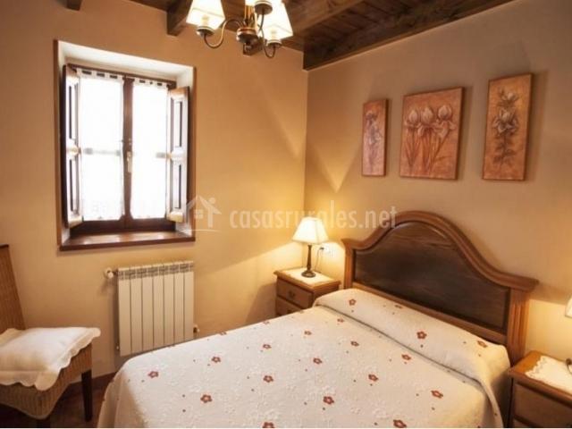 Dormitorio con cama de matrimonio y colcha con flores