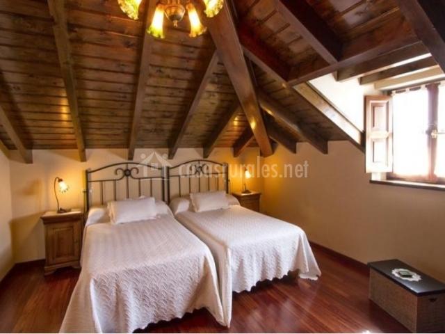 Dormitorio con camas individuales en espacio abuhardillado amplio