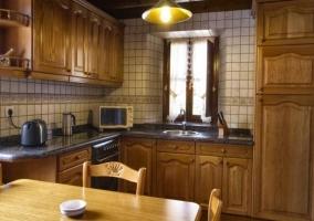 Cocina con muebles de madera y ventana en el frente principal