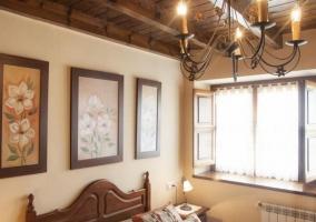Dormitorio con cama de matrimonio y tres cuadros sobre ella