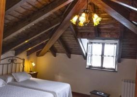 Dormitorio con camas individuales en espacio abuhardillado en madera