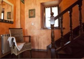 Hall recibidor con escaleras de madera junto a la ventana