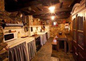 Dormitorio en madera con paredes de piedra de la casa rural