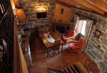 Sala de estar con mesa para comer en el centro junto a la chimenea