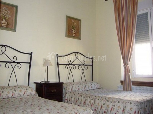 Dormitorio con camas individuales en tonos blancos y rosas y con cabeceros metálicos