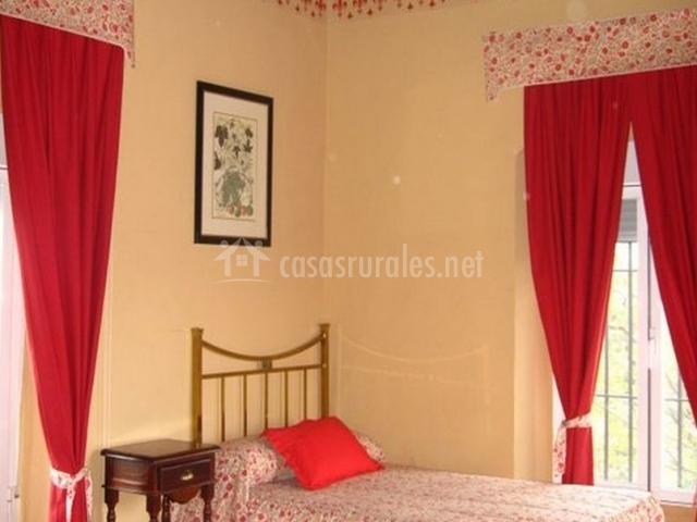 Dormitorio con camas individuales en tonos rojos florales