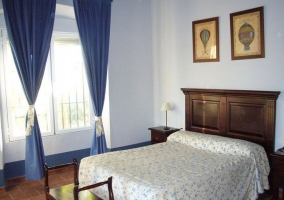 Dormitorio con cama de matrimonio en tonos azules y cabecero de madera