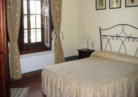 Dormitorio con cama de matrimonio en tonos marrones y con cabecero metálico