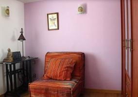 Dormitorio doble con cabeceros de madera y sofá