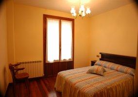 Dormitorio con cama de matrimonio y balcón