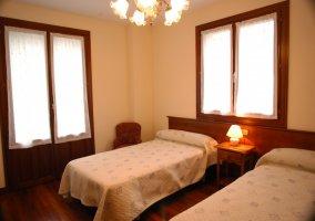 Dormitorio con dos camas y varias ventanas