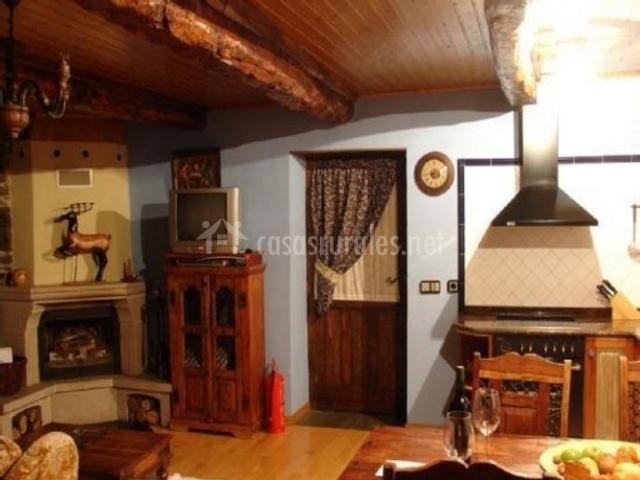 Sala de estar con chimenea y cocina comunicadas con la mesa de madera