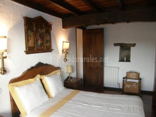 Dormitorio de matrimonio con cabecero de madera y mesilla