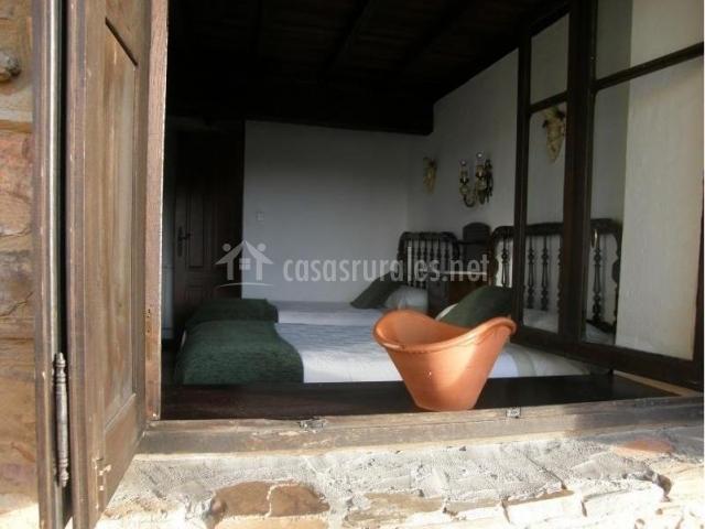 Dormitorio doble con mantas y vista desde fuera