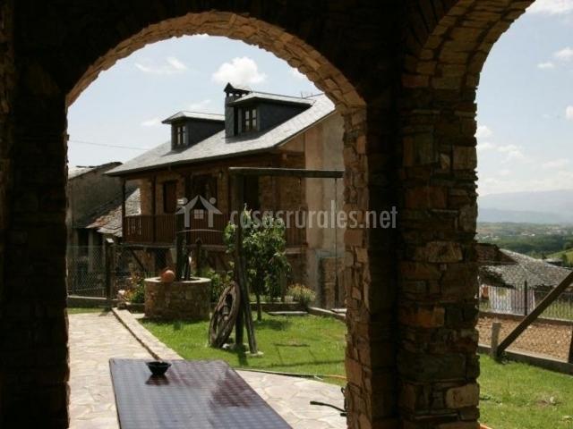 Vistas del porche con mesa y zonas verdes