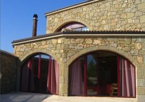 Fachada de piedra con grandes ventanales