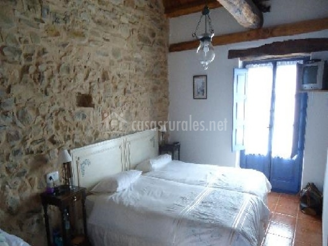 Dormitorio doble con cama supletoria colocada a un lado. Amplia ventana con cortinas azules