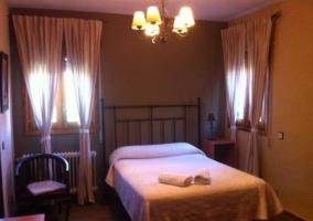 Dormitorio con cama doble de matrimonio y cabecero de hierro frojado