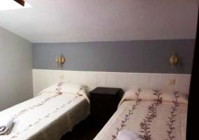 Dormitorio con dos camas individuales y cabecero de madera