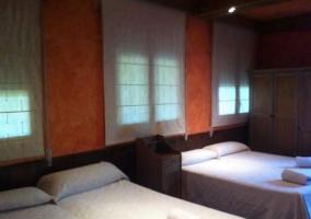 Dormitorio triple con colchas blancas