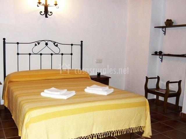 Habitación con cama de colcha amarilla