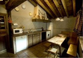 Cocina con mesa y bancos de madera