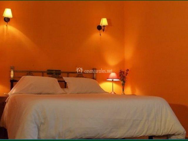 Dormitorio doble naranja con cama de matrimonio