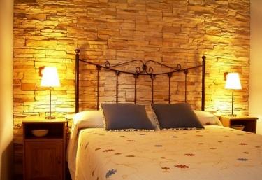 Dormitorio de matrimonio con muro de ladrillo