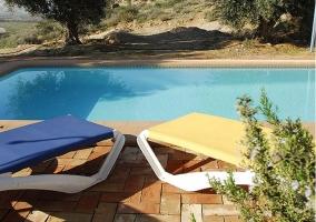 Vista de la piscina con mobiliario de exterior