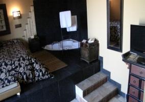 Dormitorio con televisor y bañera