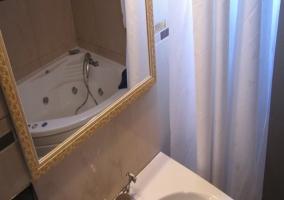 Dormitorio con aseo y espejo