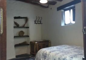 Dormitorio de matrimonio con colcha de flores y detalles en madera