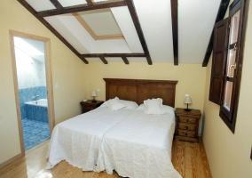 Habitación doble con cama de matrimonio y suelo de parquet