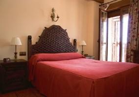 Dormitorio de matrimonio con cabecero en madera tallada