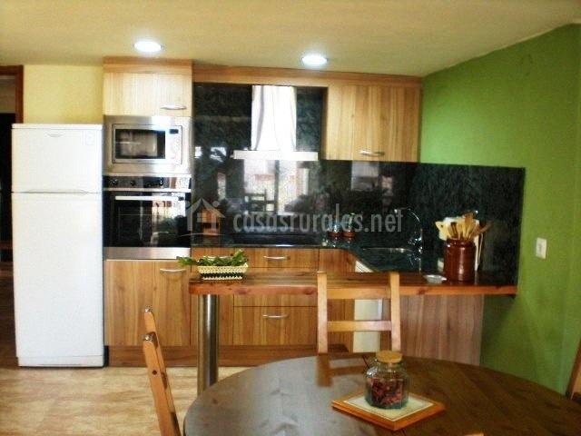 Cocina de madera con electrodomésticos y paredes verdes