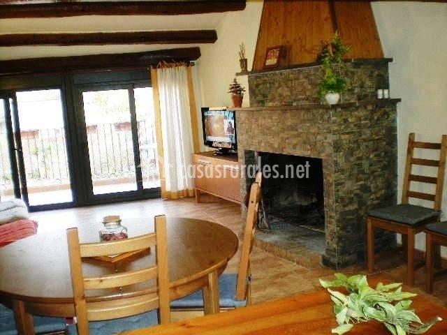 Comedor con chimenea de piedra, ventanal y mobiliario