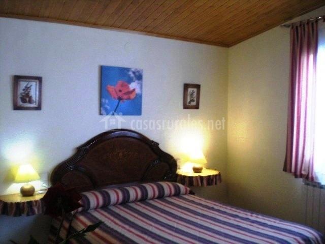 Dormitorio de matrimonio on colores morados. Lámpara encendida