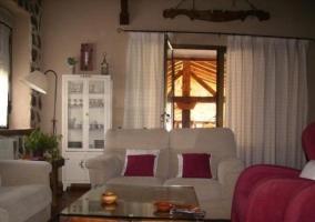 Sala de estar con paredes de piedra y sillones tapizados