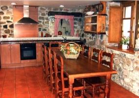 cocina con paredes de piedra y mesa para 10 personas