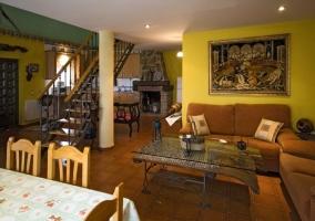 Mesa de comedor, salón y chimenea al fondo