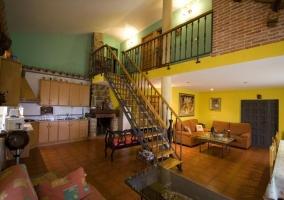 Salón, cocina y escaleras hacia los dormitorios