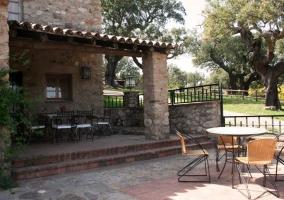 Acceso a la casa con fachada en piedra y jardines delante